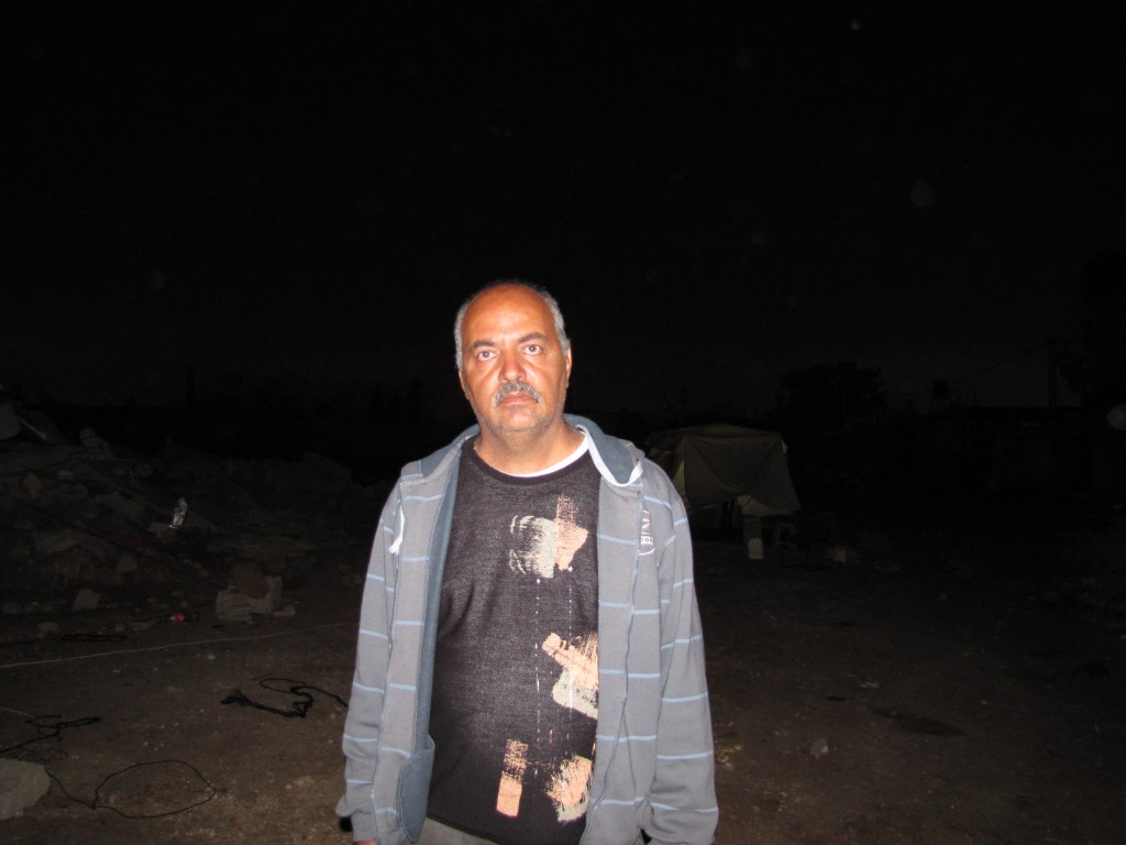Riyadh Abu Eid stands by the rubble of his home